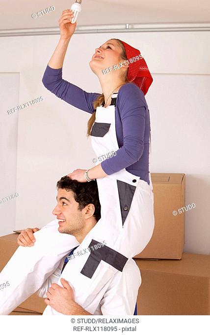 Couple new home changing light bulb piggyback fun