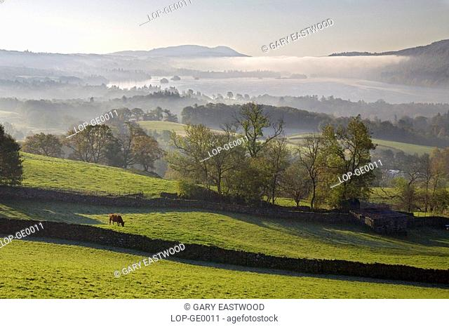 England, Cumbria, Lake Windermere. A view of morning mist hanging over Lake Windermere