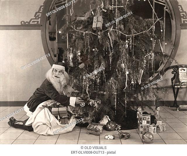 Santa Claus putting presents under Christmas trees