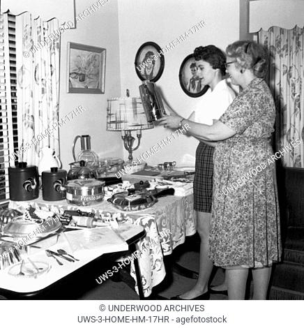 United States: c. 1961 Two women at a housewares party look at a coffe pot