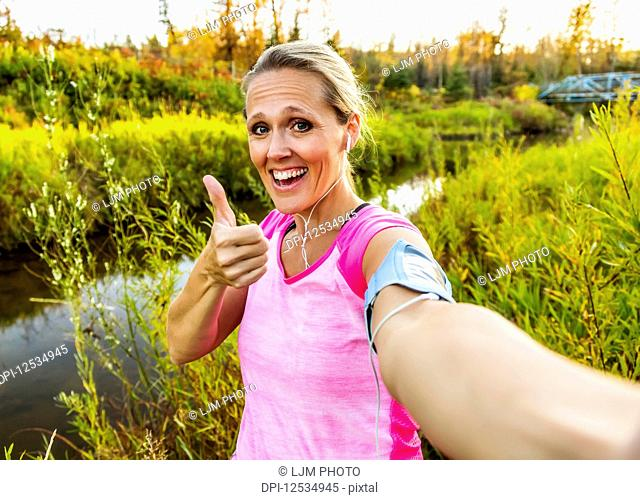 An attractive middle-aged woman wearing active wear pauses to take a selfy with a thumbs up while out running beside a creek in a city park on a warm fall...