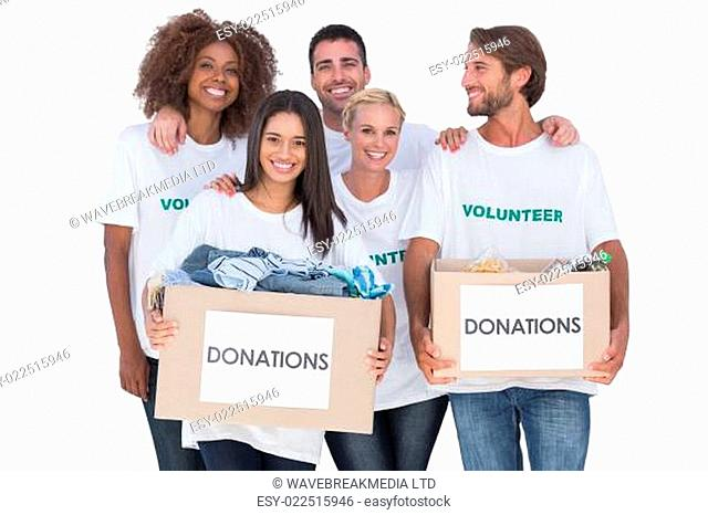 Happy group of volunteers holding clothes donation boxes on white background