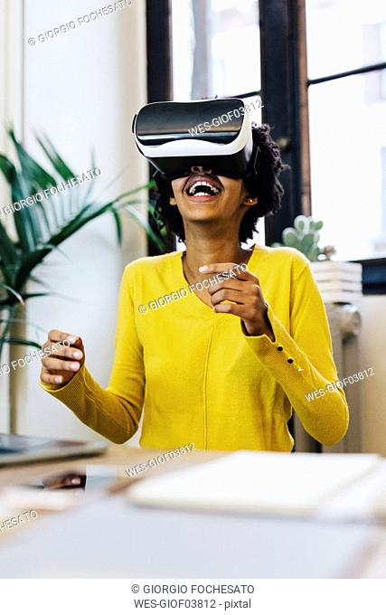 Laughing young woman playing game, wearing virtual reality goggles
