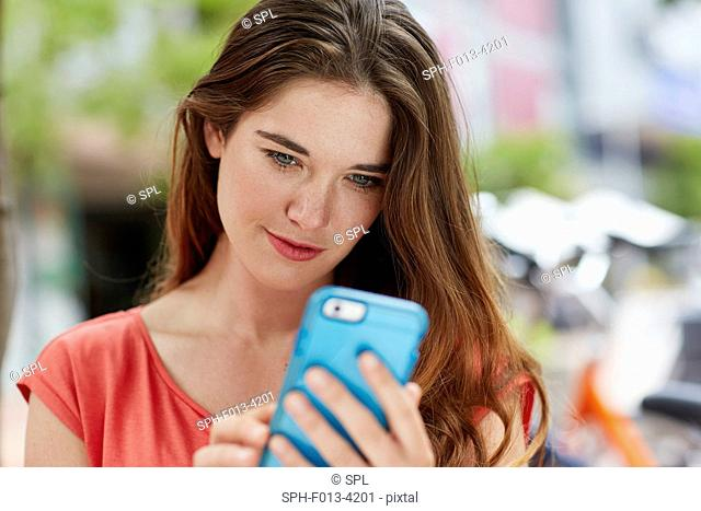MODEL RELEASED. Young woman using smartphone