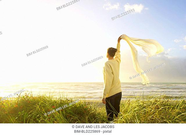 Hispanic woman standing in grass at beach waving scarf