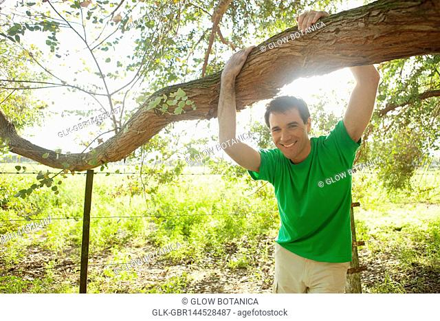 Man hanging on a tree branch