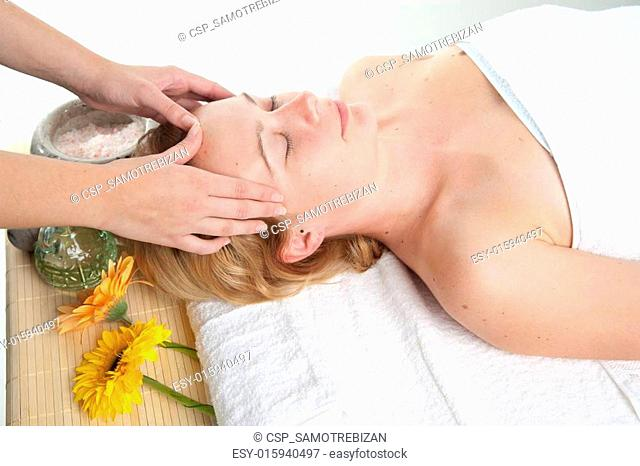 Beautiful young woman having a massage in wellness centre - girl in spa