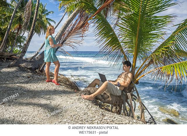 Man working on the beach. Attractive man with laptop seated in a palm tree on a tropical beach. Young man working on laptop computer on the tropical beach in a...