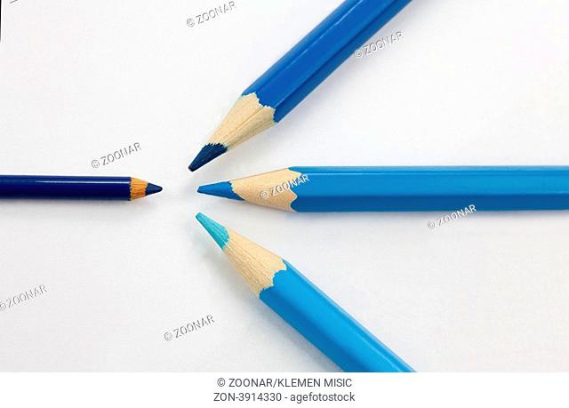 Big three blue color pencils of three different shades confronting one small dark blue color pencil against white background