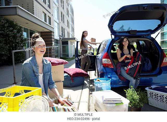 College students unloading car moving into college dorm