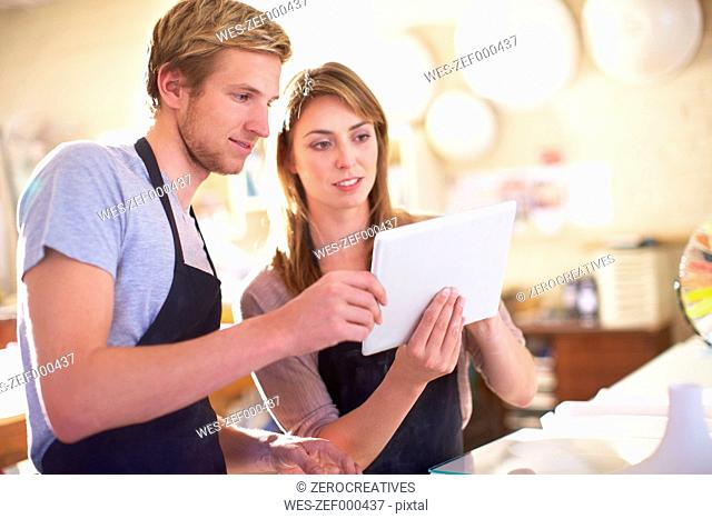 Couple in a workshop using digital tablet