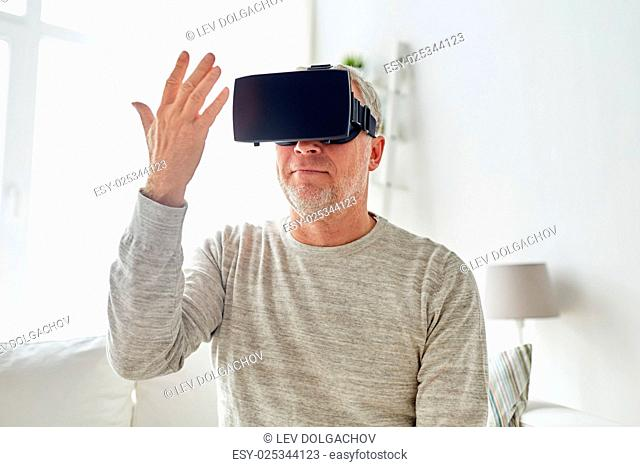 technology, augmented reality, gaming, entertainment and people concept - senior man with virtual headset or 3d glasses playing videogame and looking at his...