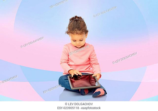 childhood, technology and people concept - little african american baby girl playing with tablet pc computer and sitting on floor over pink violet background
