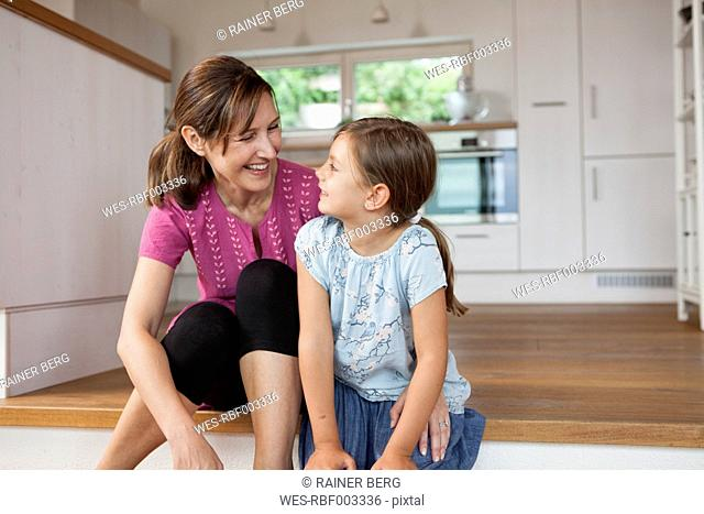 Mother and daughter sitting smiling in kitchen