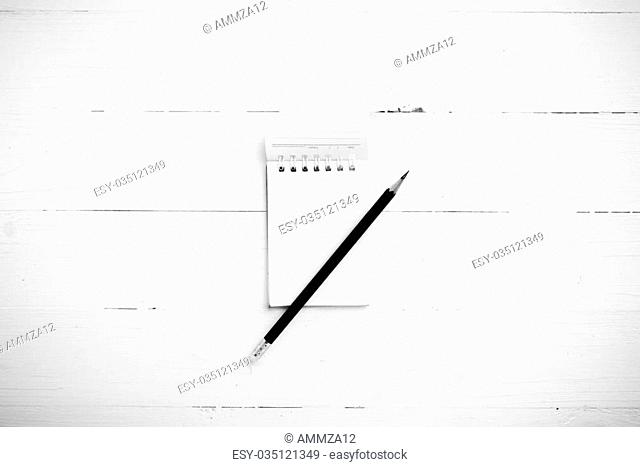 notepad with crumpled paper and pencil over white table black and white tone color style