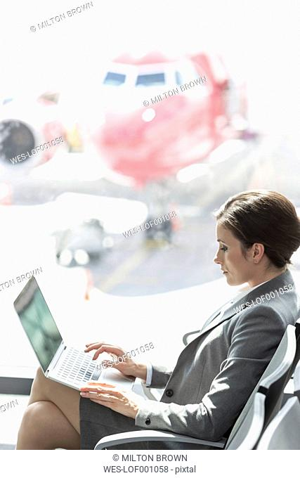 Businesswoman using laptop at the airport