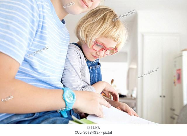 Girl and brother reading storybook in kitchen