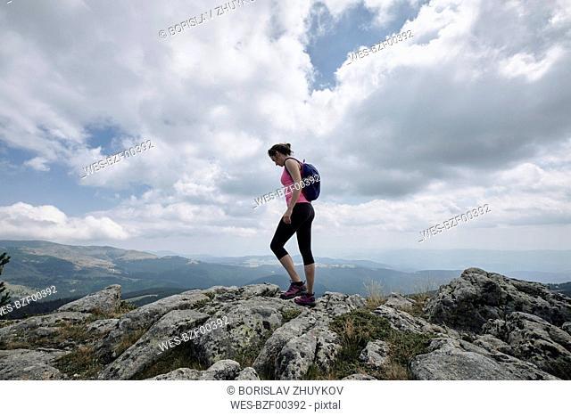 Bulgaria, Rila Mountain, female hiker standing on cliff edge
