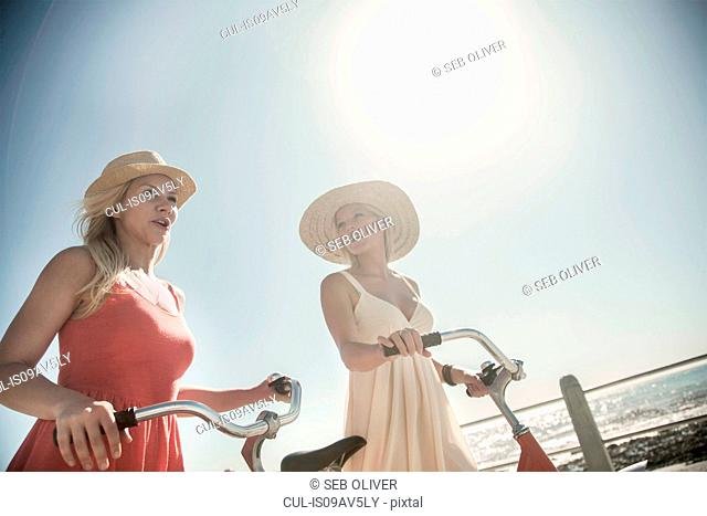 Young women walking with bicycle on seafront