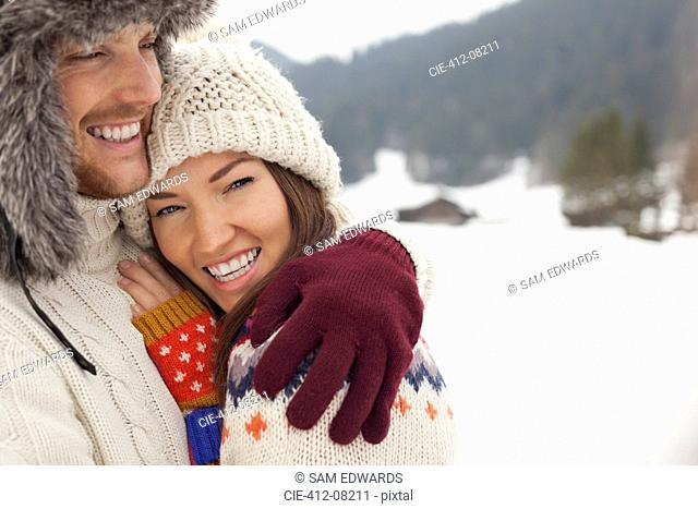 Close up portrait of happy couple hugging in snowy field