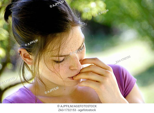 20 years old woman in a garden biting her finger nails
