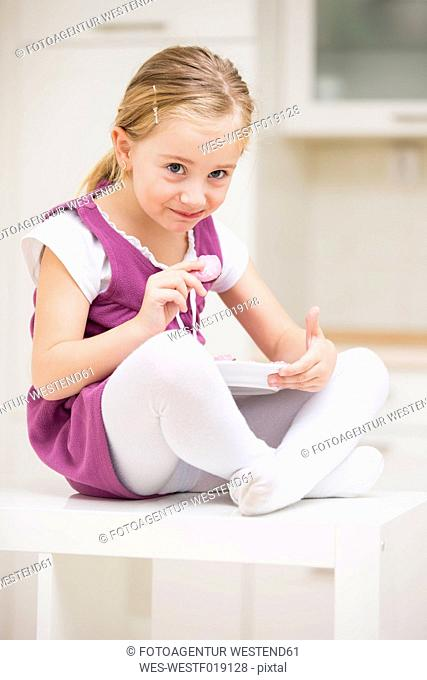 Portrait of smiling little girl sitting on a table with plate of pink cookies