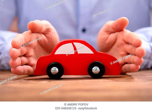 Businessman's Hand Protecting Red Toy Car On The Wooden Desk