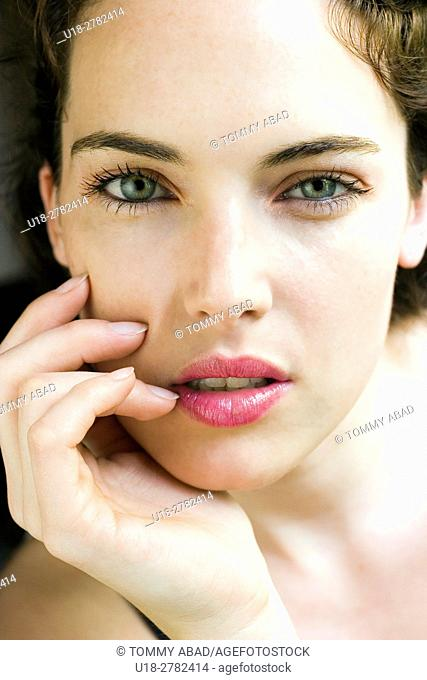 beautiful woman with green eyes looking to the camera with her hand close to her mouth