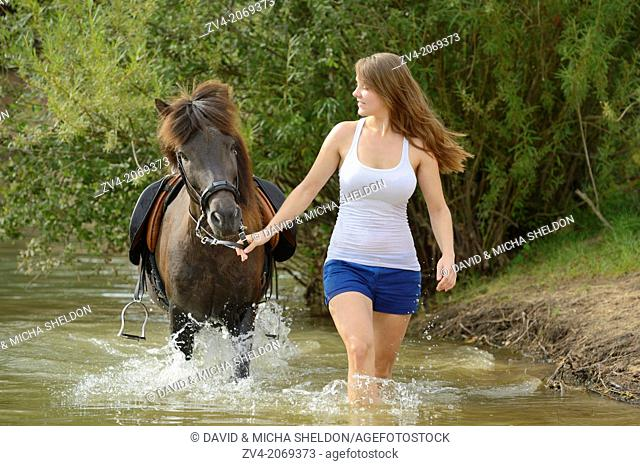 Young girl with an brown icelandic horse in summer, Bavaria, Germany
