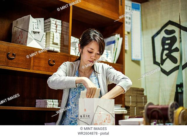 A small artisan producer of specialist treats, sweets called wagashi. A woman working packing sweet boxes for delivery
