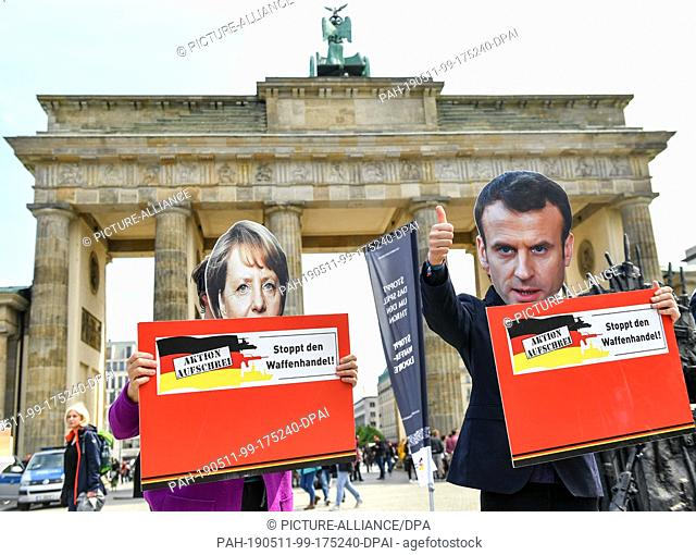 11 May 2019, Berlin: Activists with masks of the European politicians Angela Merkel (l-r, Chancellor of Germany) and Emmanuel Macron (President of France) are...