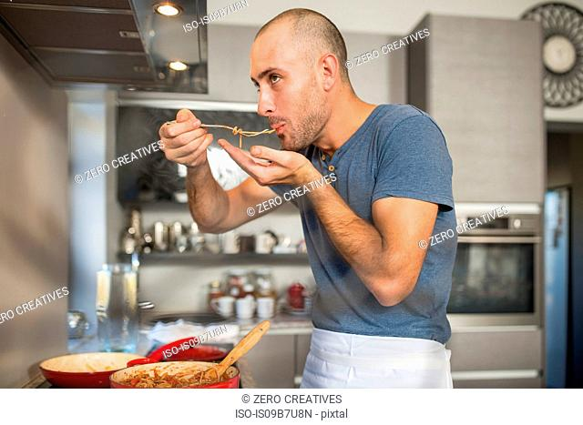 Man in kitchen, tasting food from fork, saucepan on stove in front of him