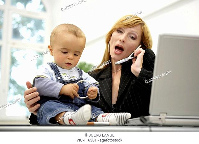 A business woman tries both to work and attend her baby in her bureau. - DRESDEN, GERMANY, 23/08/2005