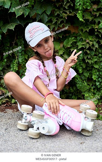 Confident little girl sticking out tongue sitting on the ground with pink roller skates