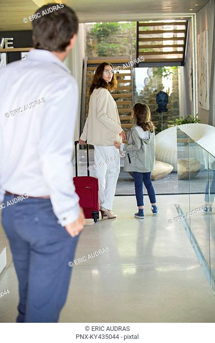 Man looking at his family leaving home
