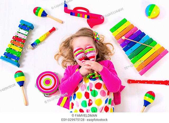 Child with music instruments. Musical education for kids. Colorful wooden art toys for kids. Little girl playing music. Kid with xylophone, guitar, flute