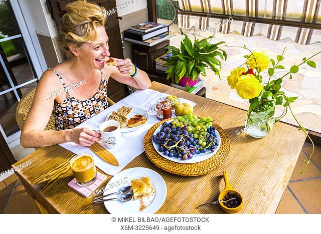 Woman taking a breakfast with toasts, cake and fruit