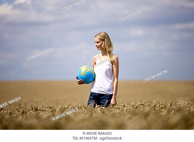 A woman standing in a wheatfield, holding a globe
