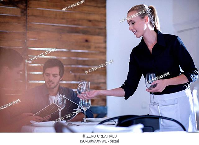 Waitress setting table with wine glass for customers