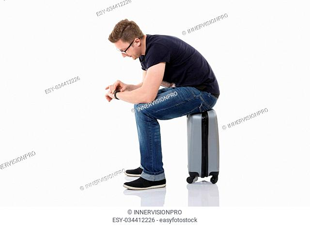 A photo of young man wating for something. He's sitting on his suitase and looking at the watch