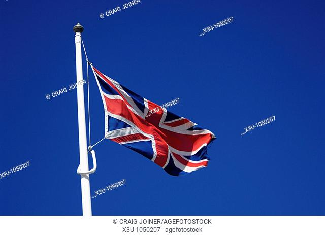 The flag of the United Kingdom flying from a white pole against a clear blue summer sky