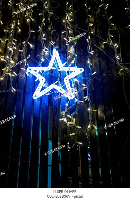 Illuminated blue star christmas light in shop window