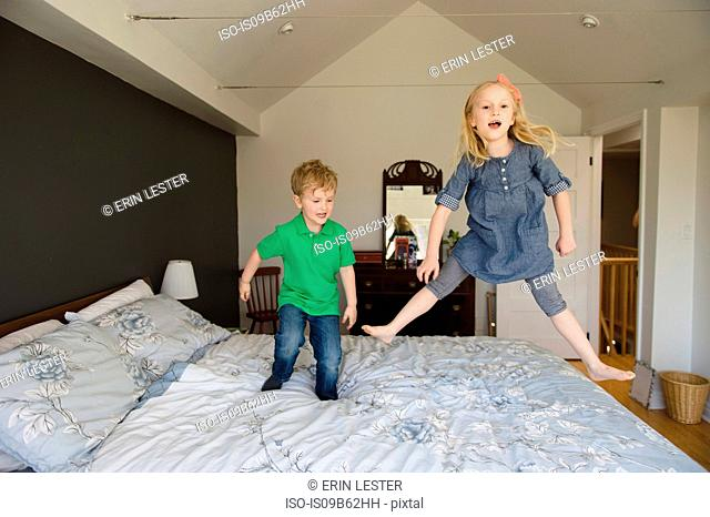 Girl and brother jumping on bed together