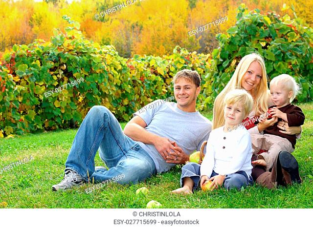 a young, attractive, happy family of four people, mother, father, baby, and young child, are sitting outside at an apple orchard