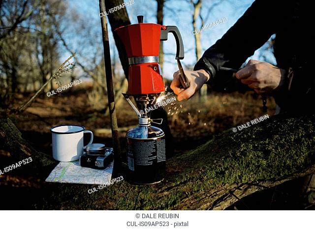 Hands of hiker igniting coffee pot on camping stove in woods
