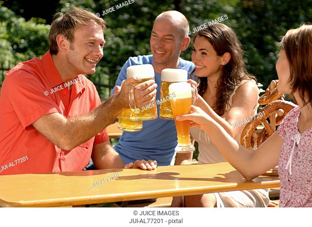 Portrait of two couples toasting each other, beergarden, Munich, Bavaria, Germany