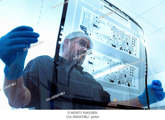 Worker inspecting circuit board negative sheet in circuit board factory