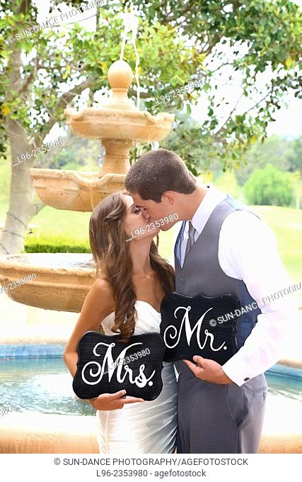 Bride and groom kissing, holding 'Mr & Mrs' signs in front of a fountain