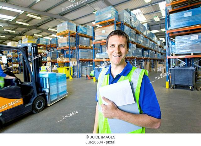 Worker in warehouse holding clipboard