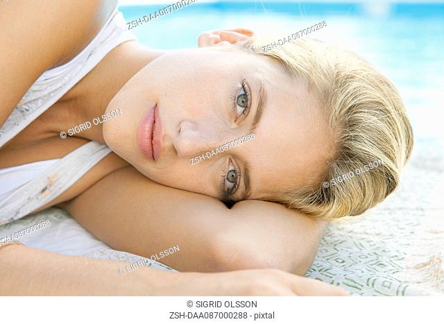 Woman relaxing at poolside, portrait